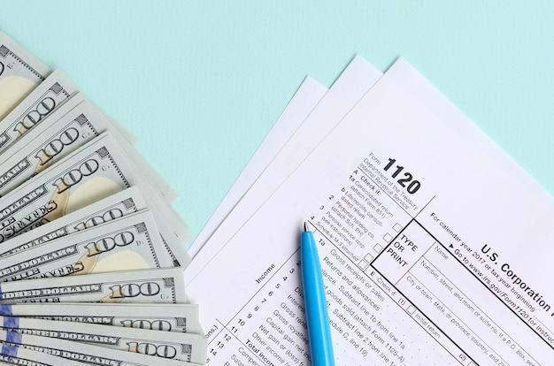 Il modulo fiscale 1120 si trova vicino a centinaia di banconote da un dollaro e penna blu su un azzurro