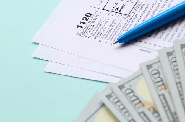 Il modulo fiscale 1120 si trova vicino a centinaia di banconote da un dollaro e penna blu