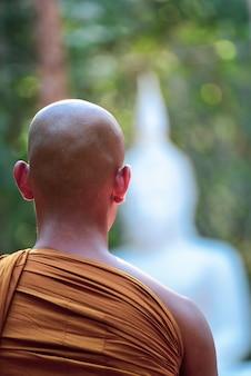 Il monaco buddista vipassana medita per calmare la mente e sfocare la statua del buddha in tailandia.