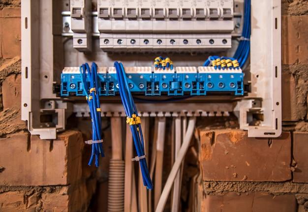 Il montaggio del quadro elettrico, lavoro elettricista, un robot con fili e interruttori