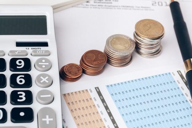 Il mucchio di soldi conia con la carta millimetrata sulla tavola di legno, nel conto, nella finanza e nella crescita del commercio