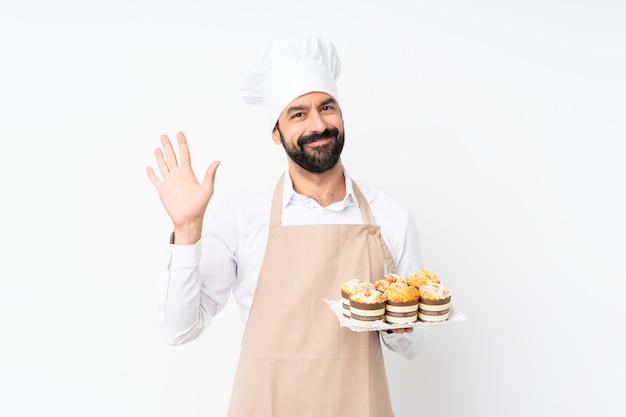 Il muffin della tenuta del giovane agglutina sopra il saluto bianco isolato con la mano con l'espressione felice