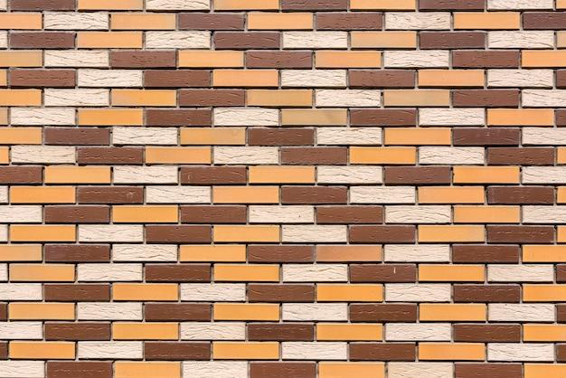 Il muro della casa è fatto di mattoni colorati decorativi sullo sfondo