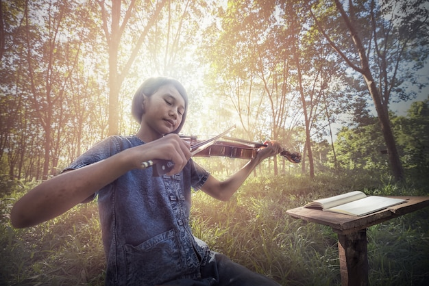 Il musical: piccolo bambino asiatico che suona il violino all'aperto