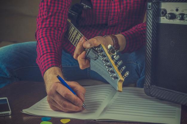 Il musicista dei pantaloni a vita bassa si siede sul divano con una chitarra elettrica e registra le note della sua melodia