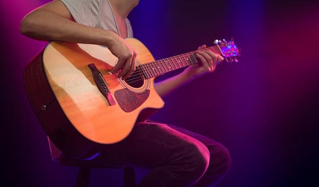 Il musicista suona una chitarra acustica.