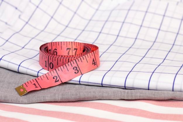 Il nastro di misurazione è in tessuto di cotone. concetto di cucito, cucito con tessuti naturali.