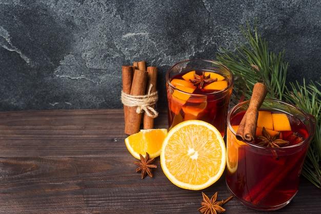 Il natale ha sciupato il vino rosso con le spezie e la frutta su una tavola rustica di legno