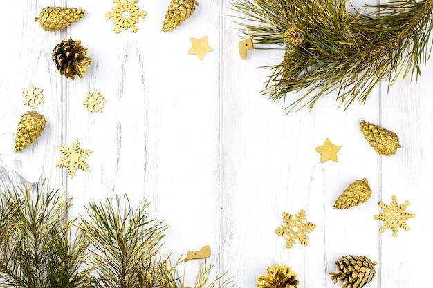 Il natale incornicia con i rami di abete, le pigne e gli ornamenti dorati su fondo di legno bianco