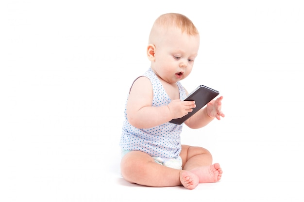 Il neonato allegro sveglio in camicia e pannolino blu tiene il cellulare