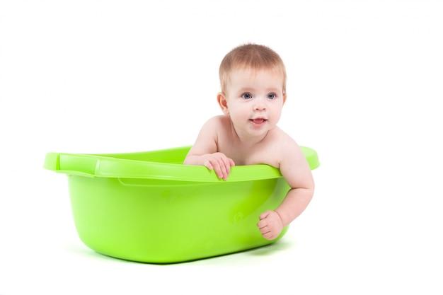 Il neonato attraente sveglio prende il bagno in vasca