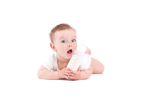 Il neonato grazioso sveglio in camicia bianca si trova sulla pancia con la bottiglia per il latte