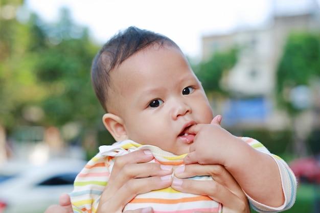 Il neonato infantile del primo piano sta succhiando il dito con il trasporto asiatico della madre.