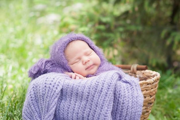 Il neonato sorridente di 17 giorni sta dormendo sul suo stomaco nel canestro sulla natura nel giardino all'aperto.