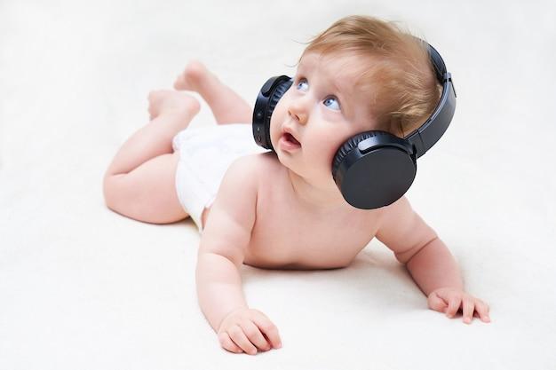 Il neonato sveglio in cuffia ascolta musica su un fondo leggero