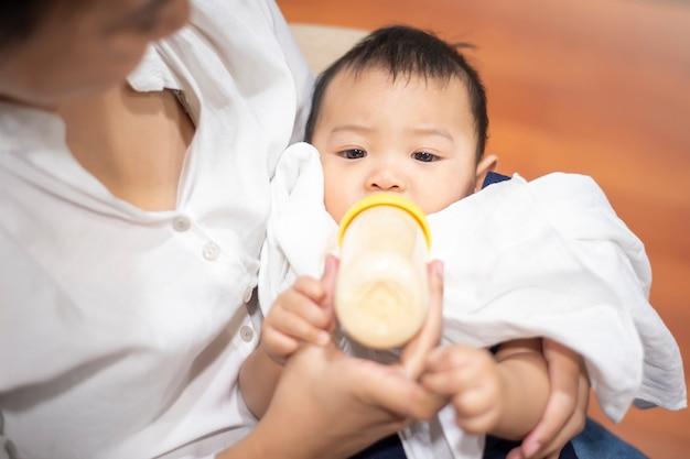 Il neonato sveglio sta bevendo il latte dalla bottiglia dalla mamma
