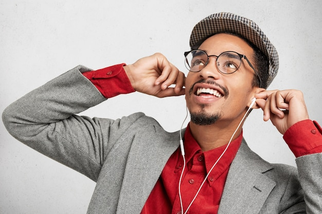 Il nerd maschio gioioso si riposa dopo aver studiato a lungo e preparato per gli esami o scritto un documento per il corso,