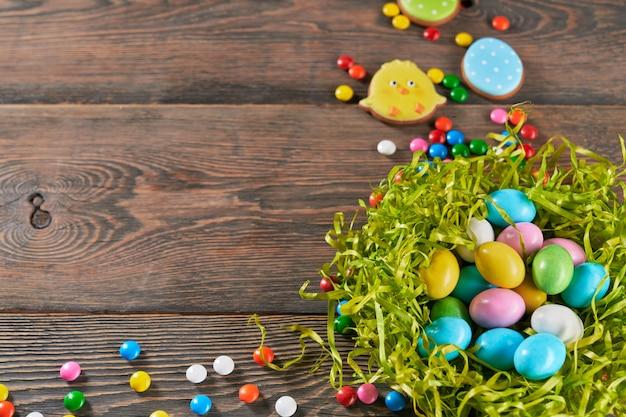 Il nido decorativo ha riempito di uova di pasqua su fondo di legno