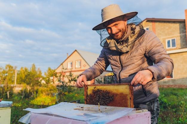 Il nonno apicoltore esperto insegna a suo nipote a prendersi cura delle api. apicoltura. il concetto di trasferimento di esperienza.