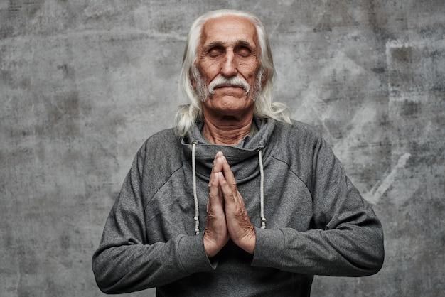 Il nonno dai capelli grigi pacificato incrociò i palmi delle mani in posizione di preghiera, meditazione, rilassamento, perdono, mantenere la calma. sfondo grigio studio