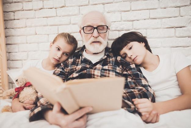 Il nonno dell'uomo anziano legge il libro per due nipoti.
