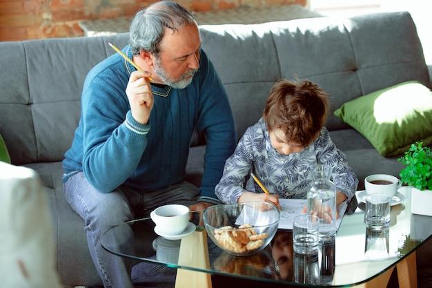 Il nonno e suo nipote trascorrono del tempo isolati a casa, studiando