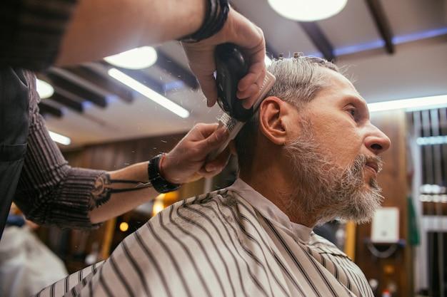Il nonno si fa tagliare i capelli dal parrucchiere nel negozio di barbiere. taglio di capelli alla moda di un vecchio pensionato