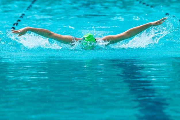 Il nuotatore femminile che lavora al suo colpo di farfalla nuota ad una piscina locale
