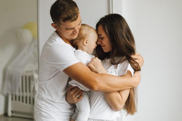 Il padre abbraccia fermamente sua moglie e un bambino