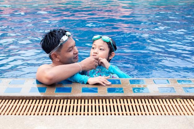 Il padre asiatico felice ciao sua figlia nella piscina