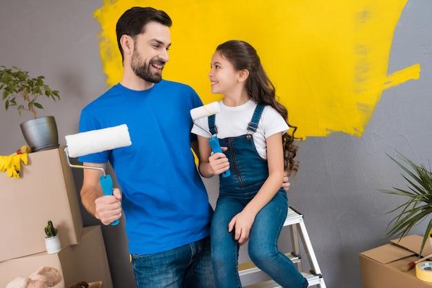 Il padre barbuto allegro e la piccola figlia progettano di dipingere la parete