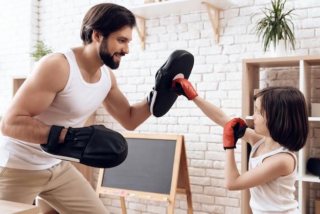 Il padre barbuto atletico insegna al figlio a inscatolare.
