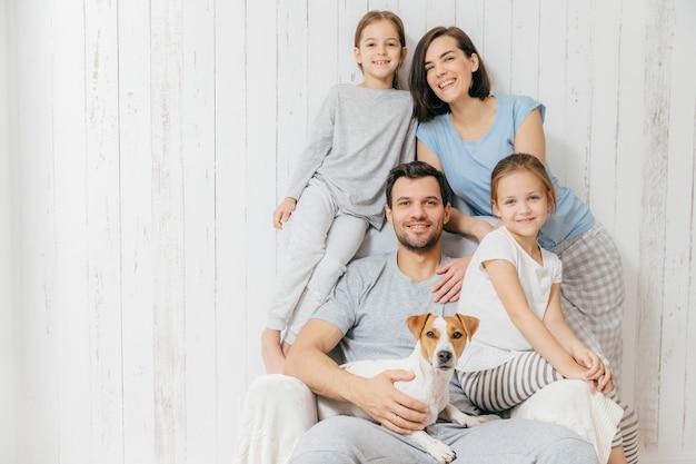 Il padre bello tiene il cane, la bella madre castana e due figlie