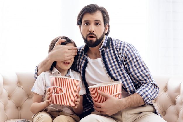 Il padre chiude gli occhi del figlio mentre guarda il film dell'orrore.