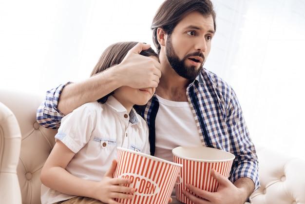 Il padre chiude gli occhi del figlio mentre guarda un film horror.