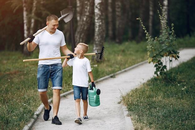 Il padre con il piccolo figlio sta piantando un albero su un parco