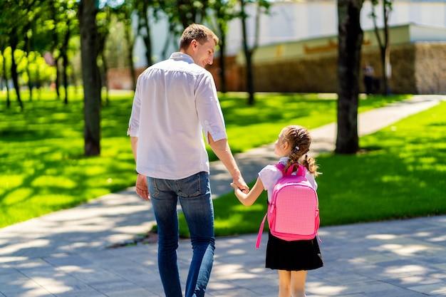 Il padre conduce la figlia a scuola in prima elementare. primo giorno a scuola. di nuovo a scuola.