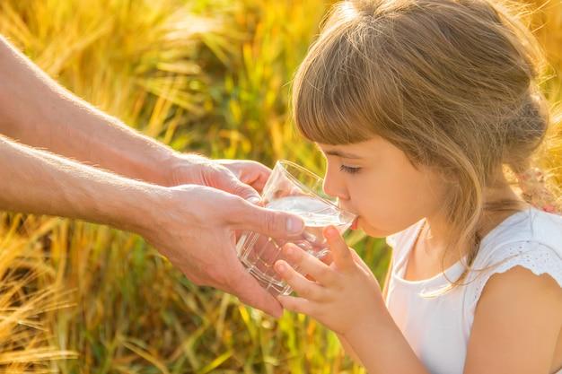 Il padre dà al bambino un bicchiere d'acqua. messa a fuoco selettiva