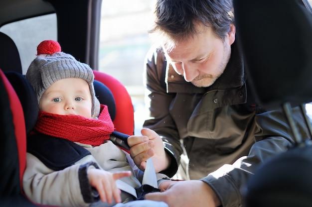 Il padre di mezza età aiuta suo figlio bambino a allacciare la cintura sul seggiolino