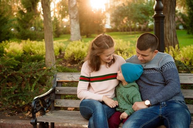 Il padre e il bambino felici della madre della famiglia sull'autunno camminano nel parco