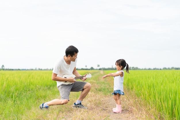 Il padre e la figlia asiatici stanno giocando le ukulele e stanno ballando insieme nel giacimento del riso