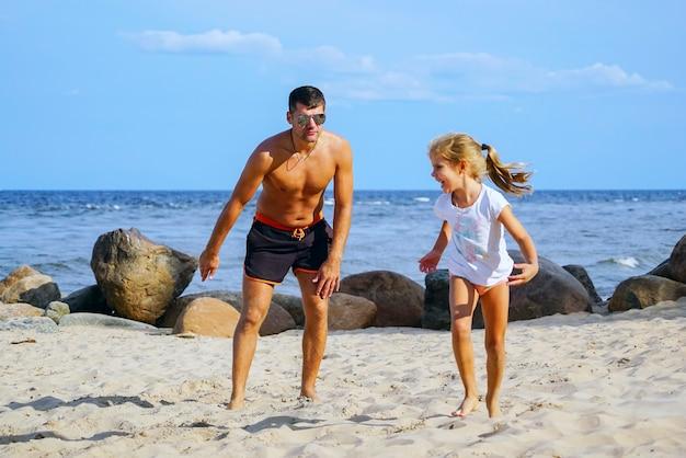 Il padre e la figlia giocano il recupero sulla spiaggia.