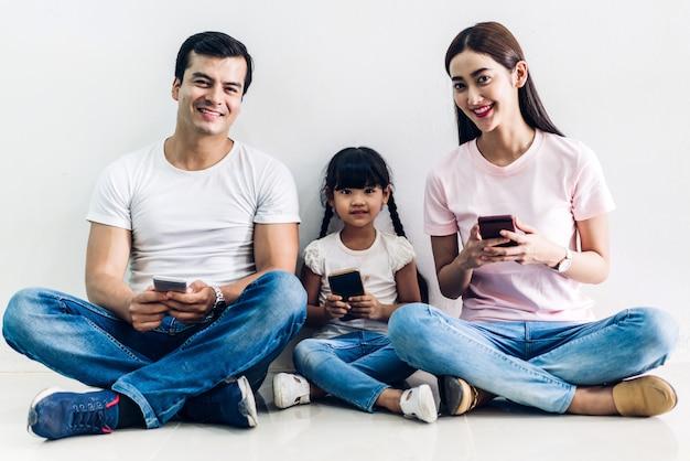 Il padre e la madre felici della famiglia con seduta della figlia e usano la tecnologia insieme dello smartphone sulla parete della parete