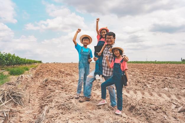 Il padre felice e due figlie e figlio che stanno sull'agricoltura terra l'azienda agricola