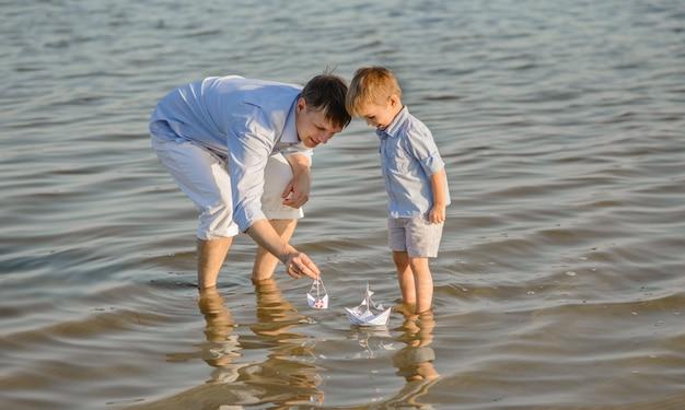 Il padre felice e il figlio iniziano la nave sull'acqua