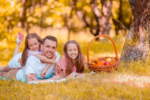 Il padre felice e le piccole figlie si rilassano sul lago