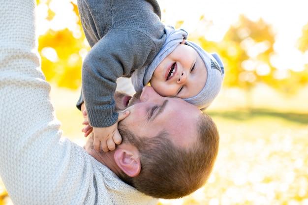 Il padre felice getta il suo bambino adorabile nel parco di autunno.