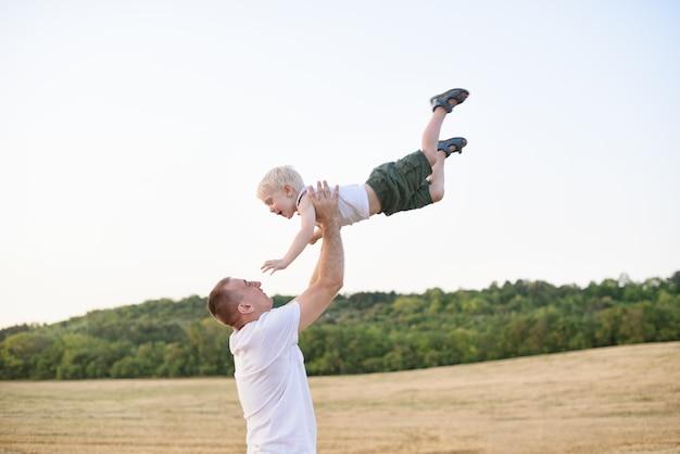 Il padre felice solleva un ragazzino biondo su un campo di grano falciato. ora del tramonto