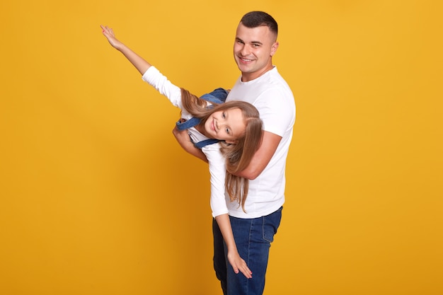 Il padre gioca con la bambina carina, il bambino vestito in abiti casual, l'uomo bello che tiene la sua piccola figlia come aereo, isolato su giallo. relazioni familiari