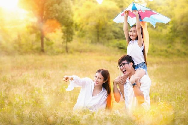 Il padre, la madre e la figlia asiatici della famiglia giocano l'aquilone nel parco all'aperto